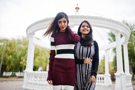 Portrait of two young beautiful indian or south asian teenage girls in dress background white temple arch.