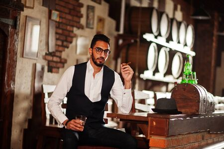 Handsome well-dressed arabian man with glass of whiskey and cigar posed at pub. Imagens