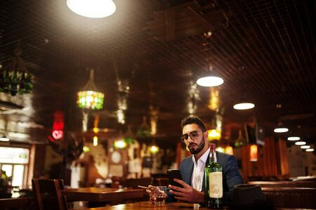 Handsome well-dressed arabian man with glass of whiskey and cigar hold mobile phone,  posed at pub. Stockfoto