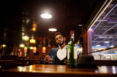 Handsome well-dressed arabian man with glass of whiskey and cigar hold mobile phone,  posed at pub. 免版税图像