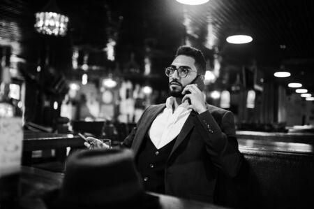 Gut aussehender, gut gekleideter arabischer Mann mit Glas Whisky und Zigarre halten Handy, posiert in der Kneipe.
