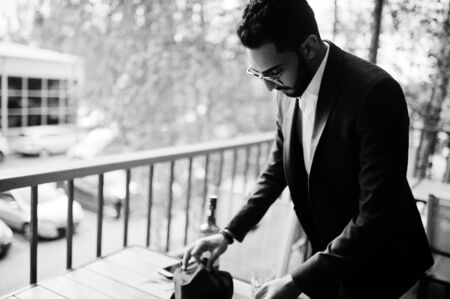 Handsome well-dressed arabian man smoke cigar at balcony of pub.