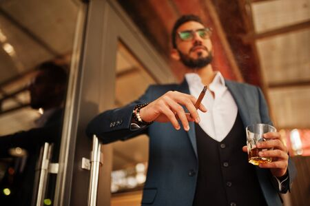 Handsome well-dressed arabian man smoke cigar with glass of whiskey at balcony of pub.