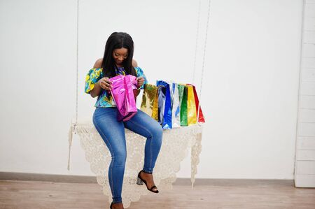Black african american millennial girl in living room hold colored shopping bags, happy dark skinned young woman. Black friday is coming.