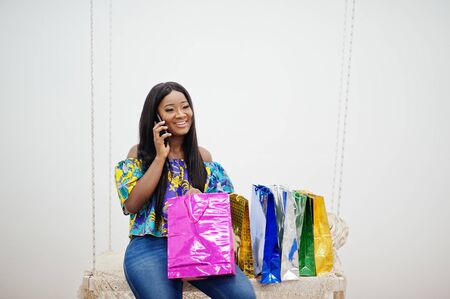 Black african american millennial girl in living room hold colored shopping bags, happy dark skinned young woman. Black friday is coming. Speak on telephone.