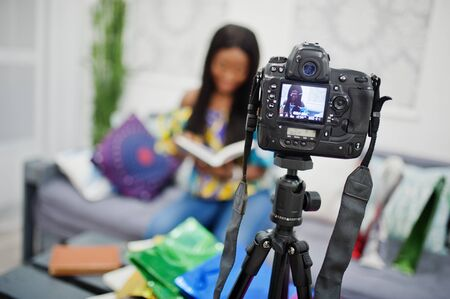 Cute african american woman making a video for her blog using a tripod mounted digital camera. Young female blogger or vlogger on camera. 版權商用圖片