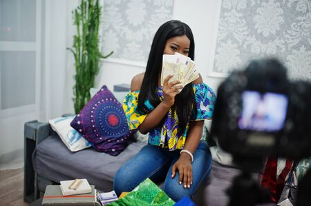 Cute african american woman making a video for her blog with money using a tripod mounted digital camera. Young female blogger or vlogger on camera.