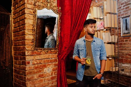Portrait of handsome successful bearded south asian, young indian freelancer in blue jeans shirt standing in cafe with cocktail against mirror.