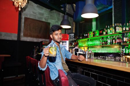 Portrait of handsome successful bearded south asian, young indian freelancer in blue jeans shirt sitting in night club against bar counter with cocktail and having a rest. 写真素材