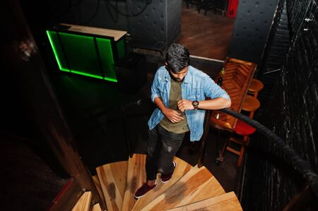 Portrait of handsome successful bearded south asian, young indian freelancer in blue jeans shirt standing in night club on stairs. 写真素材