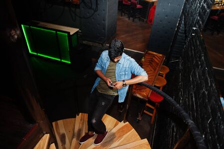 Portrait of handsome successful bearded south asian, young indian freelancer in blue jeans shirt standing in night club on stairs and look at his mobile phone.