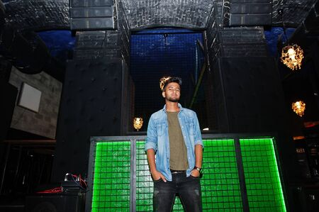Portrait of handsome successful bearded south asian, young indian freelancer in blue jeans shirt standing in night club.