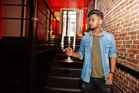 Portrait of handsome successful bearded south asian, young indian freelancer in blue jeans shirt standing in night club and hold chandelier. 写真素材