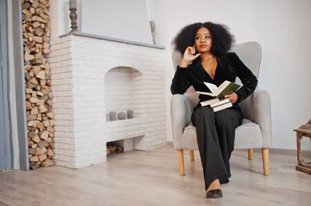 Stylish african american woman in black posed at room against fire place read books.