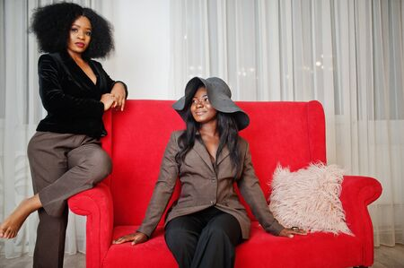Two stylish african american womans in formal wear and hat sitting on red couch at white room.