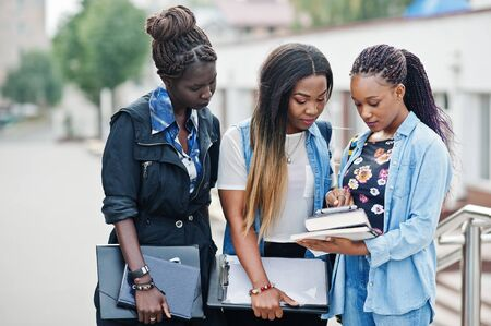 Three african students female posed with backpacks and school items on yard of university and look at tablet.