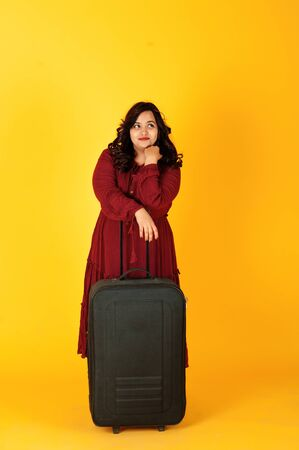 Attractive south asian traveler woman in deep red gown dress posed at studio on yellow background with suitcase. Stock Photo