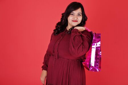Attractive south asian woman in deep red gown dress posed at studio on pink background with bright colored shopping bags. Stock Photo