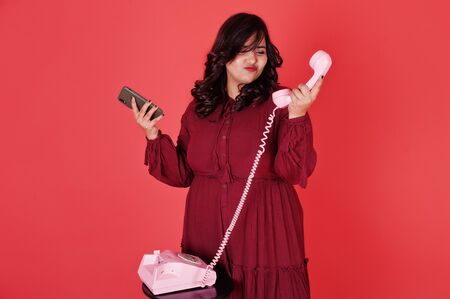 Attractive south asian woman in deep red gown dress posed at studio on pink background and use old vintage telephone with modern mobile phone. Stock Photo