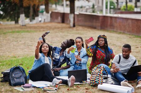 Group of five african college students spending time together on campus at university yard. Black afro friends making with mobile phones. Education theme.