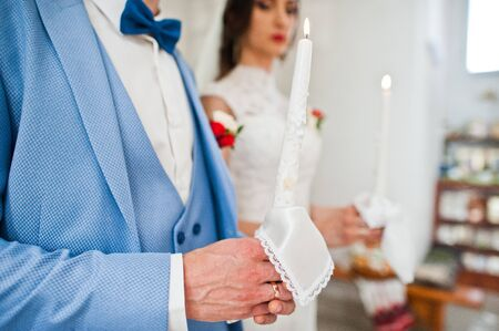 Hands of man with candle at church on wedding.