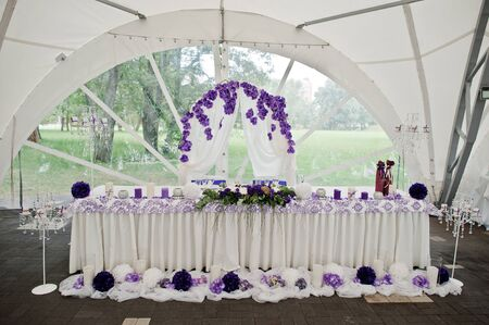 Beautiful wedding set decoration in the restaurant. Table of newlyweds outdoor tent.
