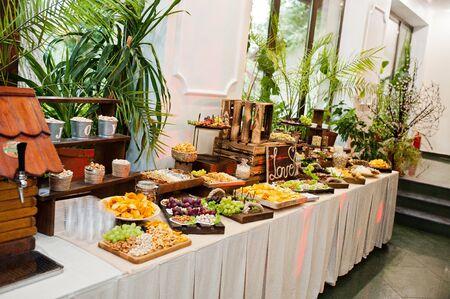 Tavolo da dessert di deliziosi snack al ricevimento di nozze. Archivio Fotografico