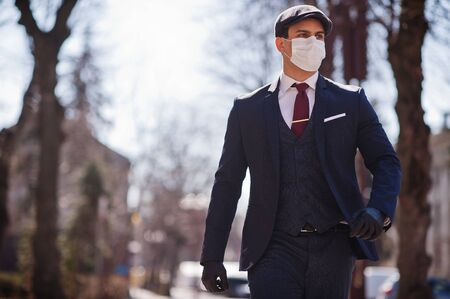 Concept of coronavirus quarantine. Business man wear on suit with medical face mask