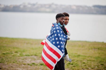 Two african teenagers friends with american flag at park wearing medical masks protect from infections and diseases coronavirus virus quarantine.