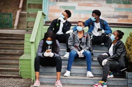Group of african teenagers friends at park wearing medical masks protect from infections and diseases coronavirus virus quarantine.