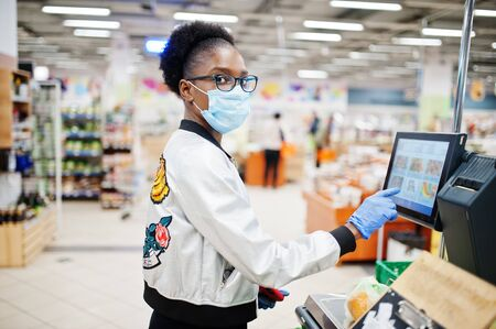 African woman wearing disposable medical mask and gloves shopping in supermarket during coronavirus pandemia outbreak. Black female weighs fruits at epidemic time.