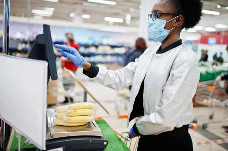 African woman wearing disposable medical mask and gloves shopping in supermarket during coronavirus pandemia outbreak. Black female weighs fruits at epidemic time. Standard-Bild