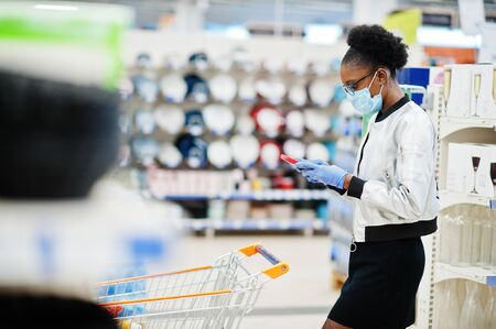 African woman wearing disposable medical mask and gloves shopping in supermarket during coronavirus pandemia outbreak. Black female with mobile phone at epidemic time.