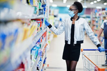 African woman wearing disposable medical mask and gloves shopping in supermarket during coronavirus pandemia outbreak. Epidemic time.