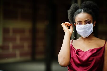 Covid-19, infectious virus. African woman with curly hair, wears red silk dress and medical disposable mask, cares about her health and protects in dangerious situation. Foto de archivo
