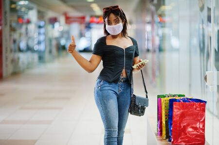 African american woman wearing face protective medical mask for protection from virus disease with mobile phone in mall during coronavirus pandemia.