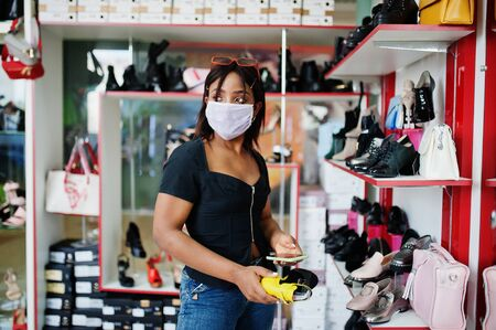 African american woman wearing face protective medical mask for protection from virus disease in shoes store during coronavirus pandemia. Stock Photo