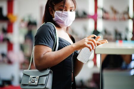 African american woman wearing face protective medical mask for protection from virus disease in shoes store use hand sanititzer during coronavirus pandemia.