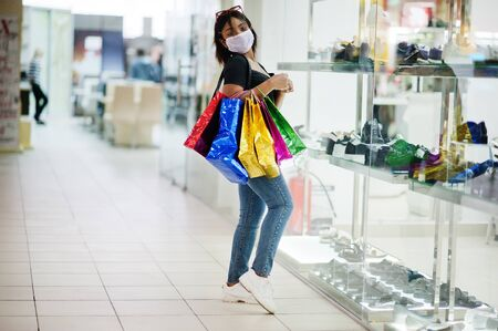 African american woman wearing face protective medical mask for protection from virus disease with shopping bags in mall during coronavirus pandemia.