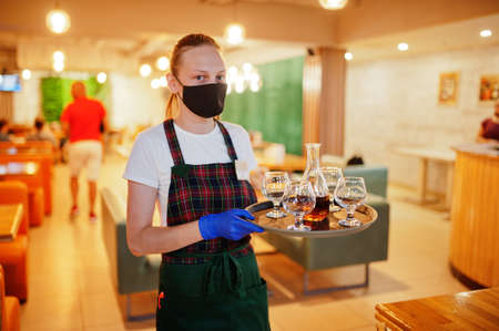 Waiter in protective mask hold tray with alcohol drink in the restaurant. Stock Photo