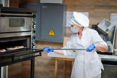 Pizza maker in protective mask working in the pizzeria. Stock Photo