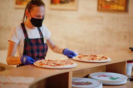 Waiter in protective mask hold pizza in pizzeria.