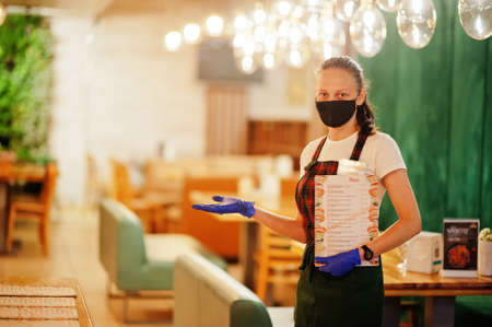 Waiter hold menu in protective mask in the restaurant. Stock Photo