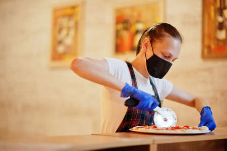 Waiter in protective mask cutting pizza in pizzeria. Stock Photo