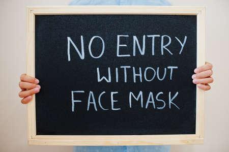 No entry without face mask. Coronavirus concept. Boy hold inscription on the board. Reklamní fotografie