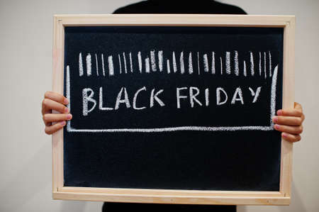 Bar code written on blackboard. Black friday concept. Boy hold board.