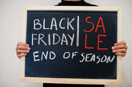 Sale end of season written on blackboard. Black friday concept. Boy hold board.