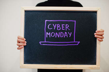 Cyber monday laptop written on blackboard. Black friday concept. Boy hold board.