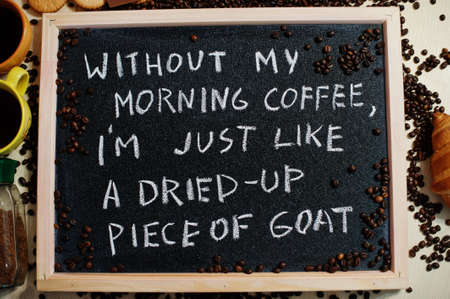 Without my morning coffee i am just like a dried-up piece of goat. Words on blackboard flat lay.