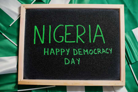 Happy democracy day of Nigeria. Text on board with nigerian flags.
